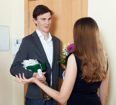 Happy man smiling and give bunch of flowers to his wife at home door