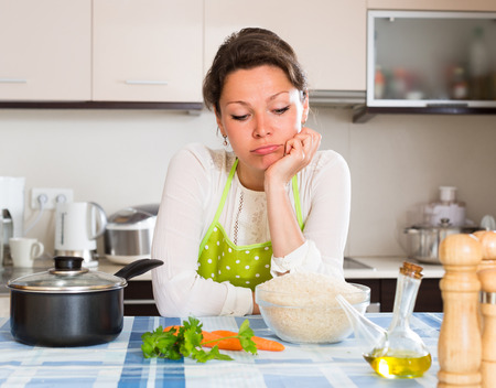 Sad lonely woman cooking rice in the kitchen