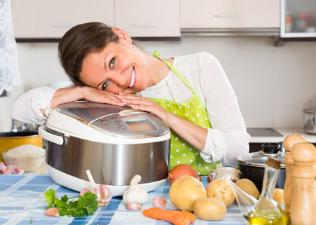 Happy young woman cooking with new multicooker in home interior photo