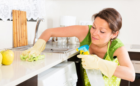 kitchen furniture: Young woman cleaning furniture in kitchen
