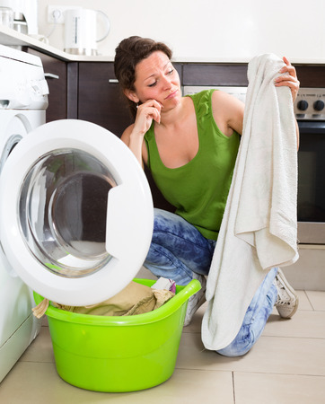 unsound: Tired girl in jeans doing laundry with washing machine at home kitchen