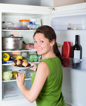 refrigerator kitchen: Smiling woman opening refrigerator with food at domestic kitchen Stock Photo