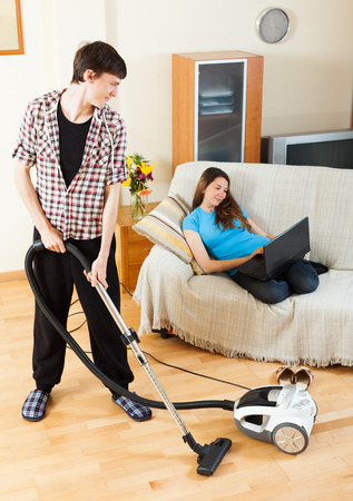 disparity: Man cleaning with vacuum cleaner  floor while wife lying with notebook over sofa at home Stock Photo