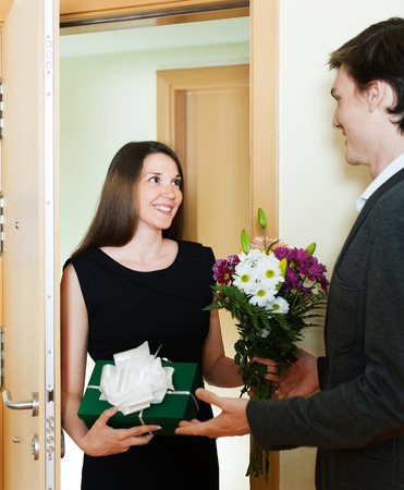 doorstep: Woman giving a gift to a man on the doorstep