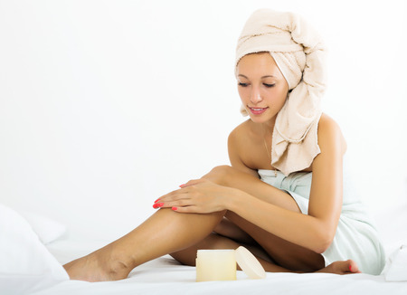 foot cream: Smiling  woman using cosmetic cream in bed Stock Photo