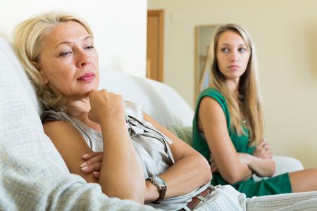 Erwachsene Tochter und verärgert Mutter mit Konflikten auf Sofa im Haus