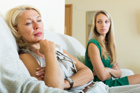 mujer llorando: hija adulta y malestar madre tener conflictos en el sof� en casa Foto de archivo