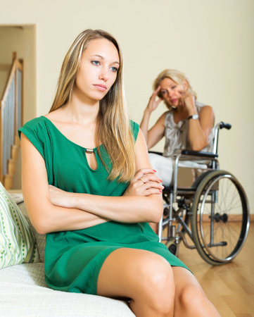 Tired woman and depressed disabled person on chair indoor photo