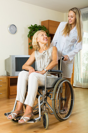 medical assistant: Smiling old woman in wheelchair with medical assistant in room