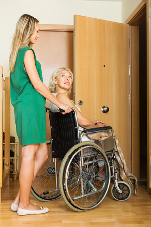 incapacitated: Friendly social worker and disabled female on chair returning home