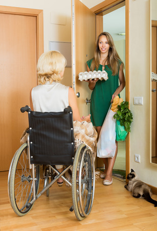 threshold: Happy woman in wheelchair meeting assistant with bags at threshold