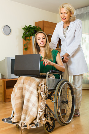 incapacitated: Smiling aged woman and handicapped girl using laptop indoor. Focus on young Stock Photo
