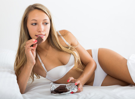 arouse: Woman in white eating chocolate in her bed
