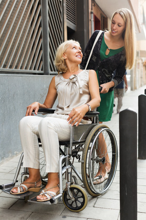 incapacitated: Female assistant  with woman in wheelchair outdoor Stock Photo