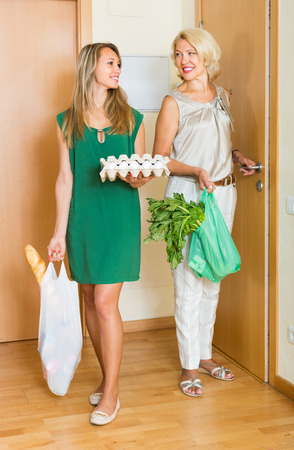 threshold: Two smiling women with food purchases in bags at threshold