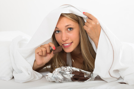 furtively: Smiling young girl eating chocolate in bed Stock Photo