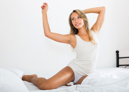 stretchy: Pretty woman smiling in her bedroom in the morning Stock Photo
