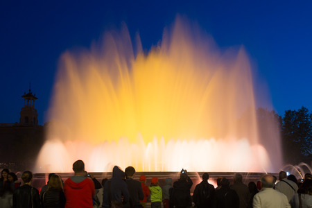 gazer: BARCELONA, SPAIN - APRIL 17, 2015: Evening view at colorful vocal fountain Montjuic show and people watching it nearby in Barcelona.