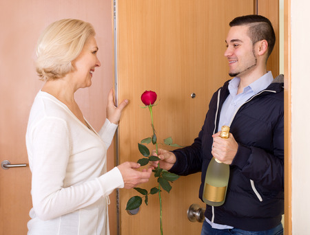 Smiling son with gifts visiting senior mother at her place