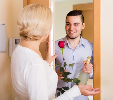 mismatch: Positive handsome man and elderly woman standing at doorway