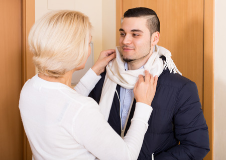 mismatch: Mature woman seeing off young boyfriend at doorway Stock Photo