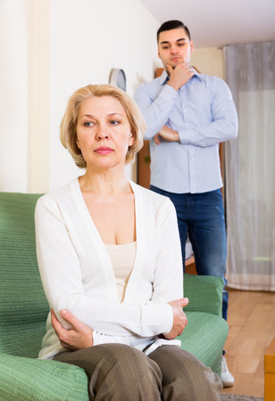 mismatch: Home conflict between sad aged woman and her young boyfriend