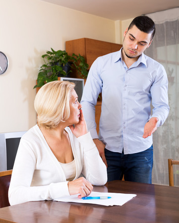 mismatch: Upset senior woman and young boyfriend with invoices for payment. Focus on the woman Stock Photo