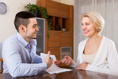 mismatch: Smiling adult son helping aged mother with documents for buying apartment. Focus on guy