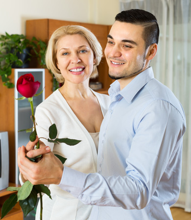 Handsome young man and mature woman slowly dancing and smiling indoor. Focus on man