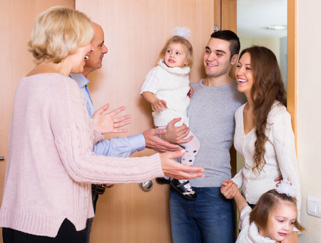 welcome people: Friendly senior people welcoming dear smiling guests with kids indoor