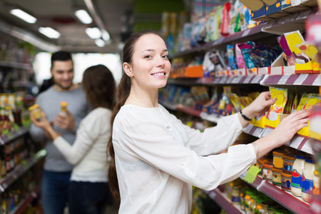 tinned: Happy adults choosing tinned food at supermarket