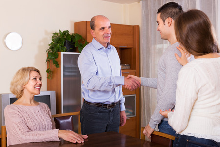Girl showing his future husband to smiling parents Stock Photo