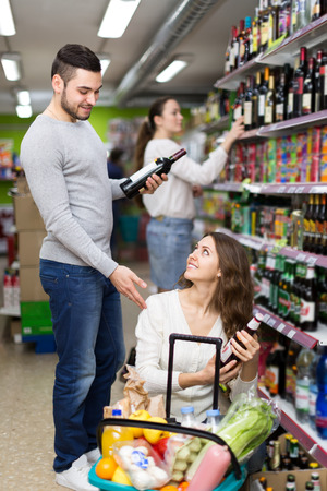 Married couple buying wine and beer in a supermarket photo