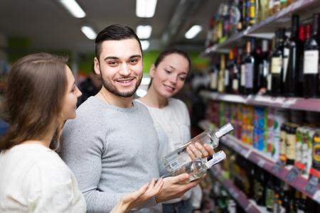 alcool: Les gens positifs debout à la section de l'alcool et de contrôle bouteille de vodka. Focus sur gars