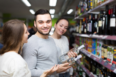 alcohol bottle: Positive people standing at alcohol section and checking vodka bottle. Focus on guy