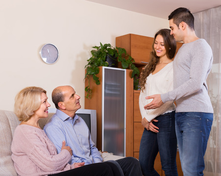 affiance: Smiling adult daughter introducing her boyfriend to her parents indoor