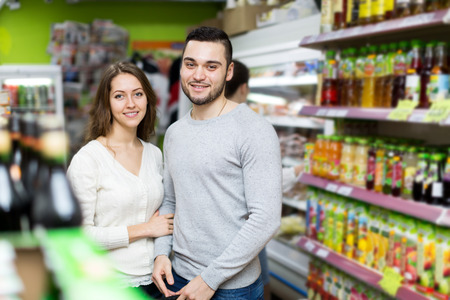 canned goods: Portrait beautiful couple standing near shelves with canned goods at shop Stock Photo