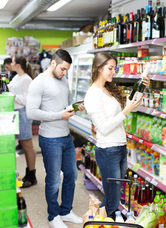 Different people choosing wine in a supermarket spirits section photo