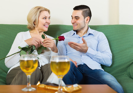 mismatch: Happy mature woman chatting with young smiling boyfriend indoors