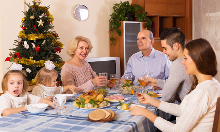 holiday gathering: Big united family at festive table near Christmas tree