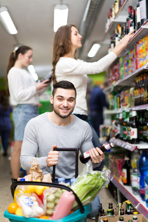 near beer: Smiling man holding a bottle of lager beer in a liquor store squatting near basket full of food Stock Photo