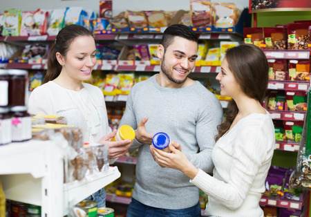 tinned: Cheerful young adults choosing tinned food at supermarket