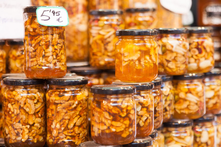 assortment of honey with nuts on counter in market photo