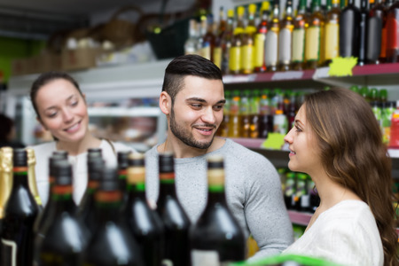 Adult positive shoppers choosing bottle of wine at liquor store photo