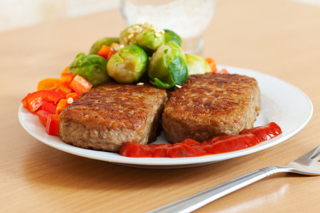 tomato catsup: Fast food. Two fried cutlets with vegetables on plate at table Stock Photo