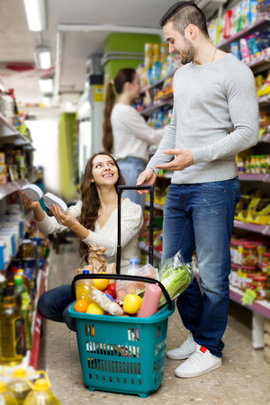 canned goods: Young happy couple standing near shelves with canned goods at shop. Focus on the woman Stock Photo