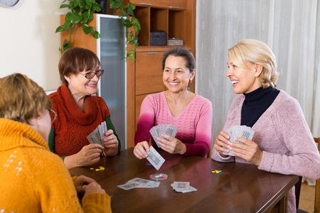 mature women: Happy smiling senior mature women playing cards at home Stock Photo