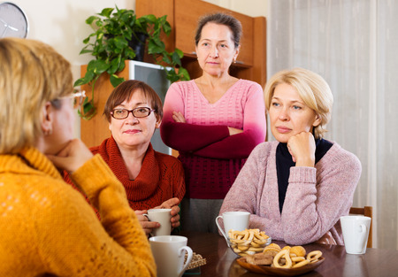 chat group: sad senior female friends  problems at table