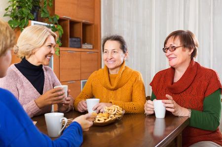 mature women: Mature women having cup of hot tea indoor and smiling