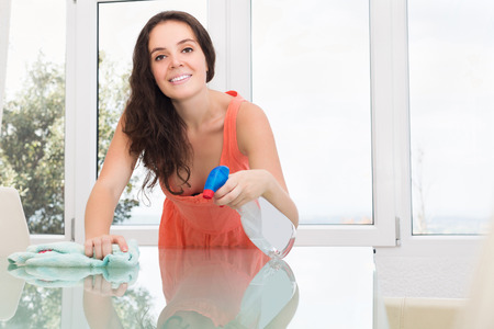 cleanser: Happy young woman dusting glass table with rag and cleanser at home
